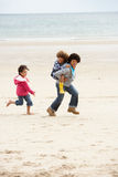 Happy children playing piggyback on beach. Smiling royalty free stock photo