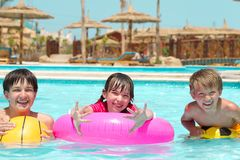 Happy children playing in pool. Happy young brothers and sister playing with inflatables in hotel swimming pool; parasols in background Stock Images