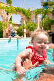 Happy children playing in the pool Stock Images