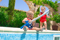 Happy children playing in the pool Stock Photography