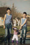 Happy children playing in the puddle Stock Photography