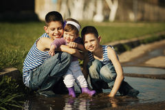 Happy children playing in the puddle Royalty Free Stock Photography