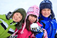 Happy children playing in snow. Three children wearing winter coats and hats, playing in the snow Royalty Free Stock Image