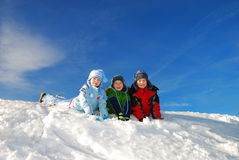 Happy Children Playing in Snow. Three smiling children playing in the snow on a bright, sunny day Royalty Free Stock Image