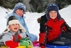 Happy children playing in snow. A view of three happy children playing in the snow on a cold winter day Royalty Free Stock Photos