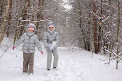 Happy children playing with snow in winter forest, family winter weekend. Outdoors Stock Photo