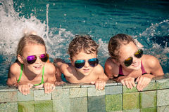 Happy children  playing on the swimming pool at the day time Royalty Free Stock Images