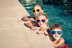 Happy children  playing on the swimming pool at the day time. Three happy children  playing on the swimming pool at the day time. Concept of friendly family Stock Photography
