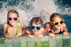 Happy children  playing on the swimming pool at the day time. Three happy children  playing on the swimming pool at the day time. Concept of friendly family Royalty Free Stock Photos