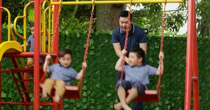 Happy children playing on swing with father. Two happy children playing on the swing with their father at the park. Shot in 4k resolution stock video footage