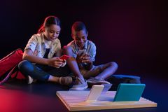 Happy children playing with their gadgets Royalty Free Stock Image