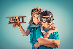 Happy children playing with toy airplane. Happy kids playing with vintage wooden airplane outdoors. Portrait of children against summer sky background. Travel Stock Image
