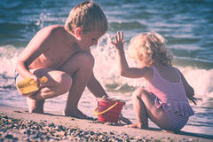 Happy children playing with toys and sand. Instagram stylisation. Little brother and sister playing with toys and sand on a sea beach. Happy children. Instagram Stock Photography