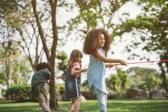 Happy children playing tug of war royalty free stock images
