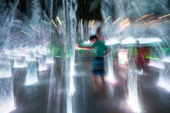 Happy children playing in a water fountain in evening lights royalty free stock image