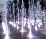 Happy children playing in a water fountain in evening lights royalty free stock photography