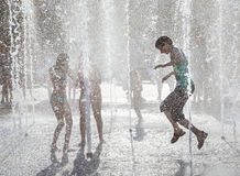 Happy children playing in a water fountain in a hot day Stock Photos