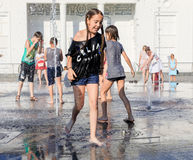 Happy children playing in a water fountain in a hot day Royalty Free Stock Photos