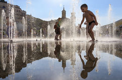 Happy children playing in a water fountain in a hot day Stock Photo