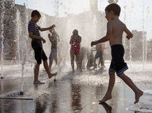 Happy children playing in a water fountain in a hot day Royalty Free Stock Photo