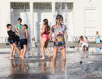 Happy children playing in a water fountain in a hot day Royalty Free Stock Photography