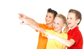Happy children point by finger on something away. stock image