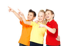 Happy children point by finger on something away. Stock Photos