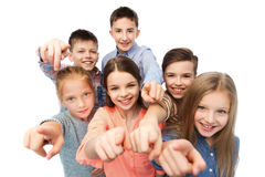 Happy children pointing finger to you. Childhood, fashion, friendship and people concept - happy smiling children pointing finger to you Royalty Free Stock Image