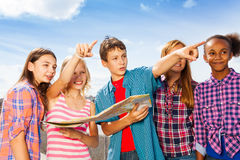 Happy children pointing with map standing close Stock Photos