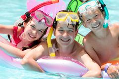Happy children in pool. Happy young brothers and sister with face masks and snorkels in swimming pool Royalty Free Stock Image