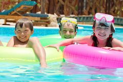 Happy children in pool. Happy young brothers and sister playing with inflatable rings in swimming pool Royalty Free Stock Photos