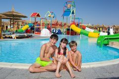 Happy children by pool. Happy young brothers with sister by swimming pool; colorful, water slides or chutes in background Stock Photo