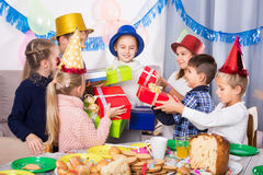 Happy children presenting gifts to girl birthday Royalty Free Stock Photography