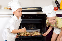 Happy children putting their pizzas in the oven Royalty Free Stock Images