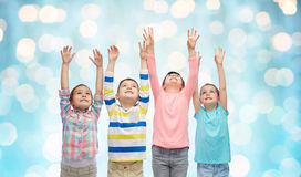Happy children with raised hands over blue lights. Childhood, fashion, gesture and people concept - happy smiling children raising fists and celebrating victory Stock Image