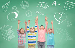 Happy children raising hands over green blackboard. Childhood, school, education, gesture and people concept - happy smiling children raising hands and Royalty Free Stock Images