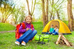 Happy children relax near the wooden bonfire, tent Stock Images