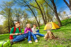 Happy children rest together near wooden bonfire Royalty Free Stock Image