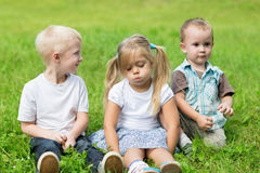 Happy children are resting on the lawn Royalty Free Stock Photography
