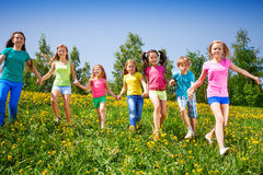 Happy children run and hold hands in green field. In summer stock photography