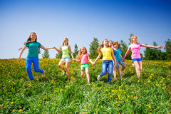 Happy children run and hold hands in green meadow. During summer stock photo