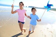 Happy children running on the beach with swirls Stock Photo