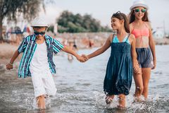 Happy children running together through the water  and holding hands at the beach royalty free stock images