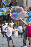 Happy children running towards a soap bubble Royalty Free Stock Image