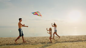 Happy children`s games. The elder brother is playing with his sisters, is launching a kite stock video footage