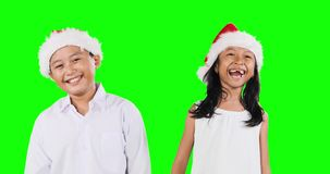 Happy children with Santa hat laughing together. Two happy children wearing Santa hat and laughing together while standing in the studio with green screen stock footage