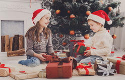 Happy children in santa hats unwrapping christmas presents Royalty Free Stock Photography