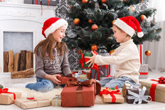 Happy children in santa hats unwrapping christmas presents Stock Photography