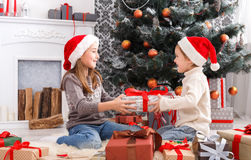 Happy children in santa hats unwrapping christmas presents Royalty Free Stock Images