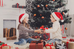 Happy children in santa hats unwrapping christmas presents Royalty Free Stock Photo